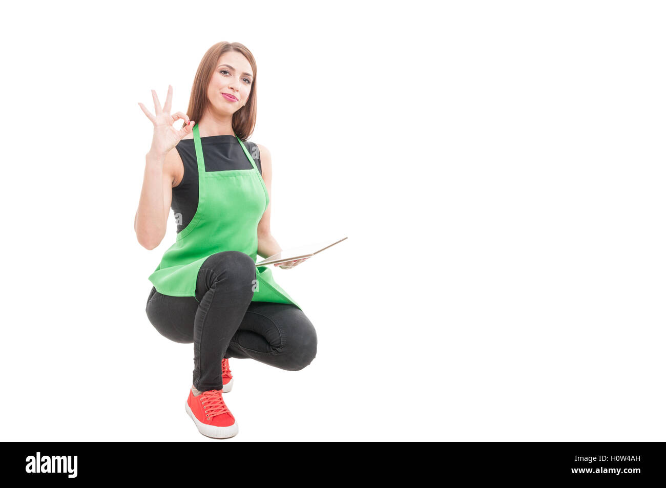 Young female seller doing ok sign as great stock results isolated on white with copyspace - Stock Image