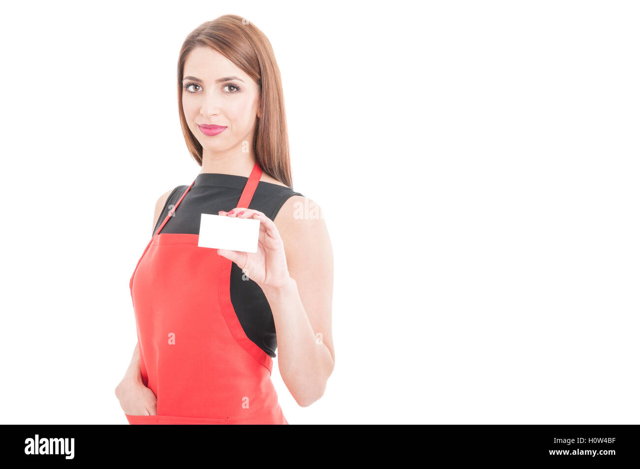 Pretty employee with red apron showing empty business card on white background with text area - Stock Image