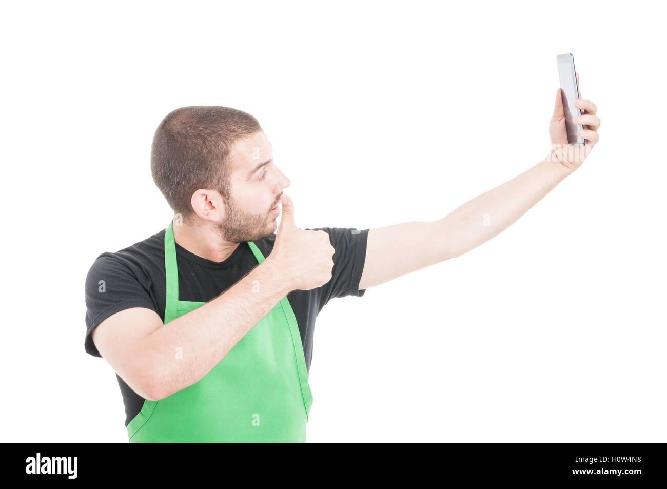 Young supermarket seller making selfie with thumb up gesture isolated on white background with copy text space - Stock Image