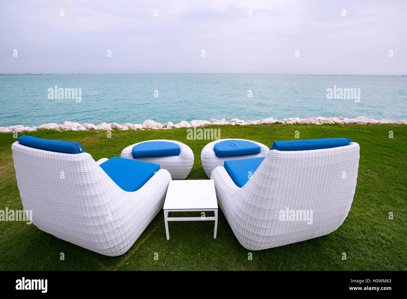 Two white sun loungers beside the sea in Doha Qatar - Stock Image