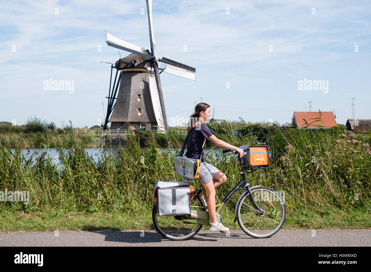 Young woman delivering mail on bicycle for Postnl with windmill to rear at Kinderdijk UNESCO World Heritage Site - Stock Image