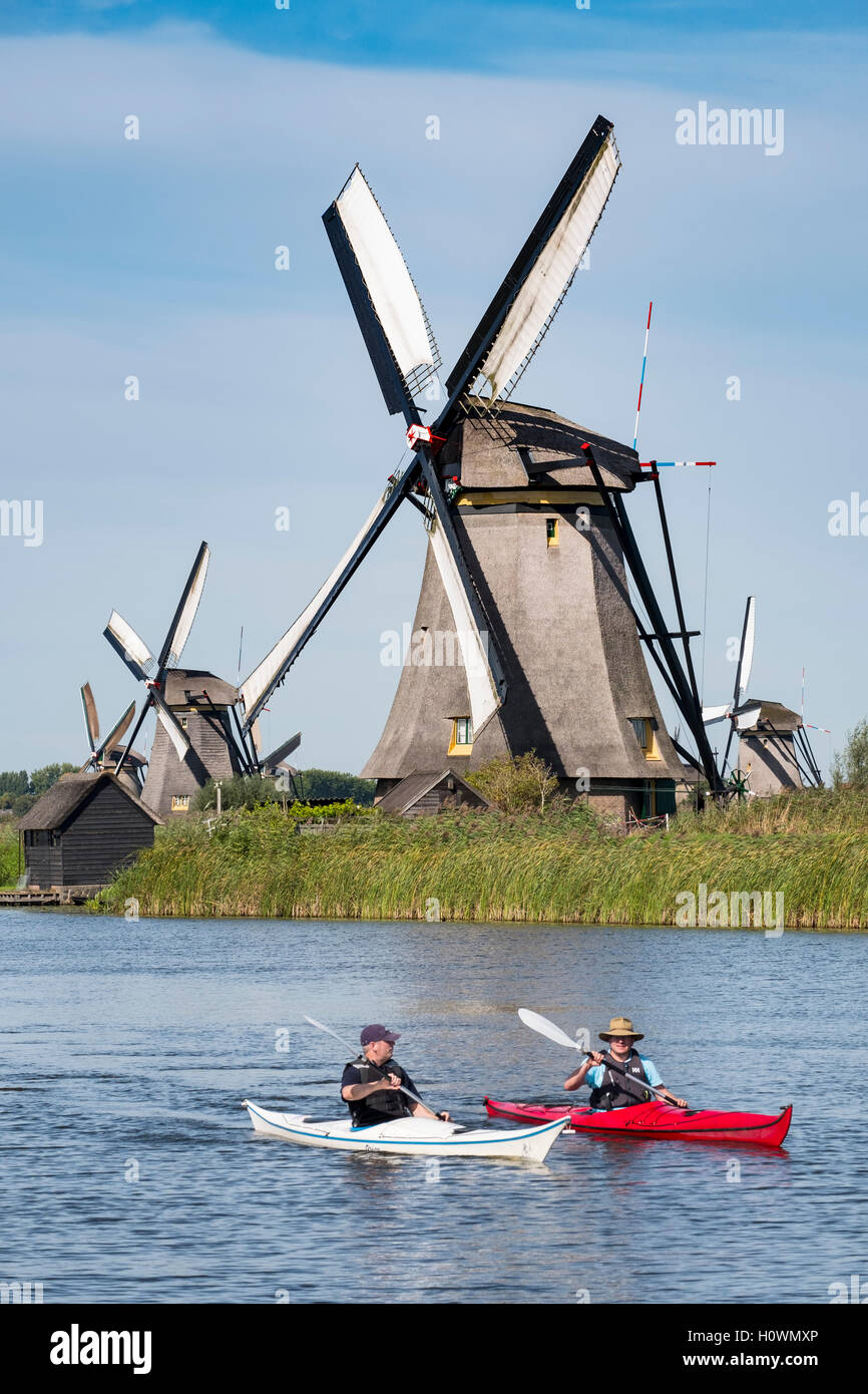 Two men in kayaks in canal in front of historic windmills at Kinderdijk UNESCO World Heritage Site in The Netherlands - Stock Image