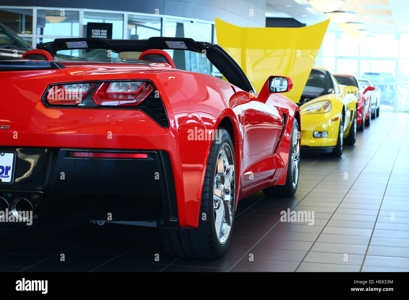 row of chevy corvette sports cars sit on display in dealership showroom, waiting to be sold Stock Photo