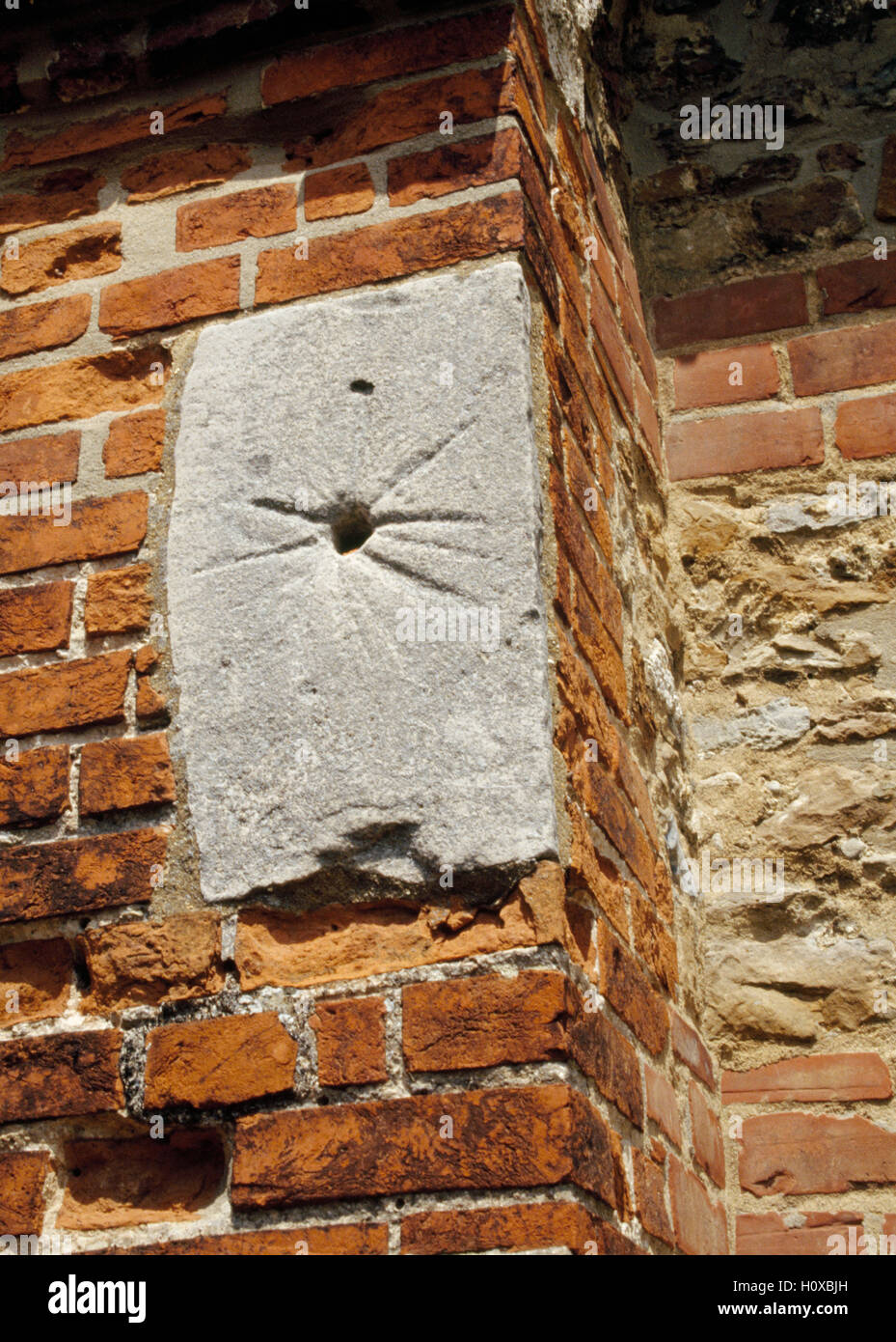 Medieval stone sundial or Mass dial set into a buttress beside the porch of  St Andrew's church, Ashingdon, - Stock Image