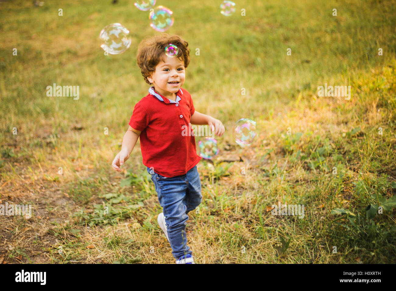 Little boy playing in the park with bubbles - Stock Image