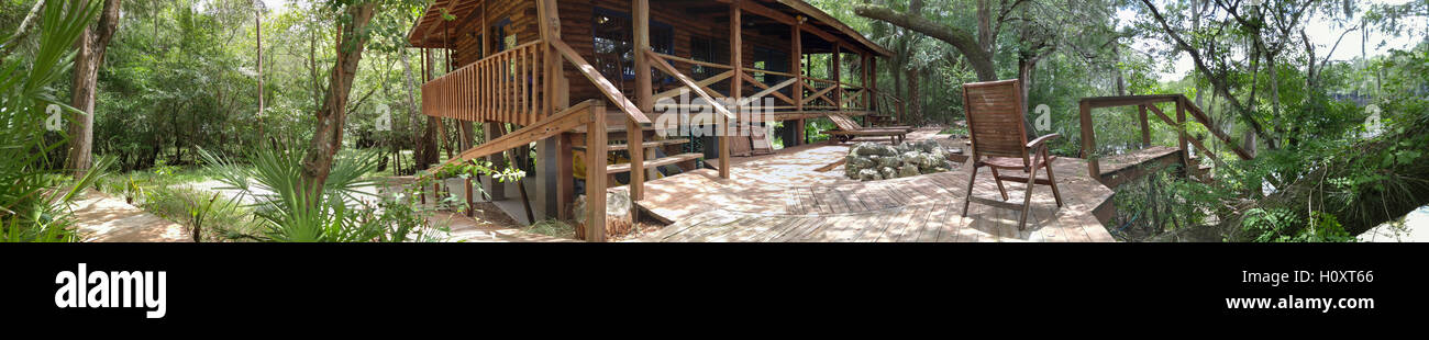 Panorama of log cabin on river - Stock Image