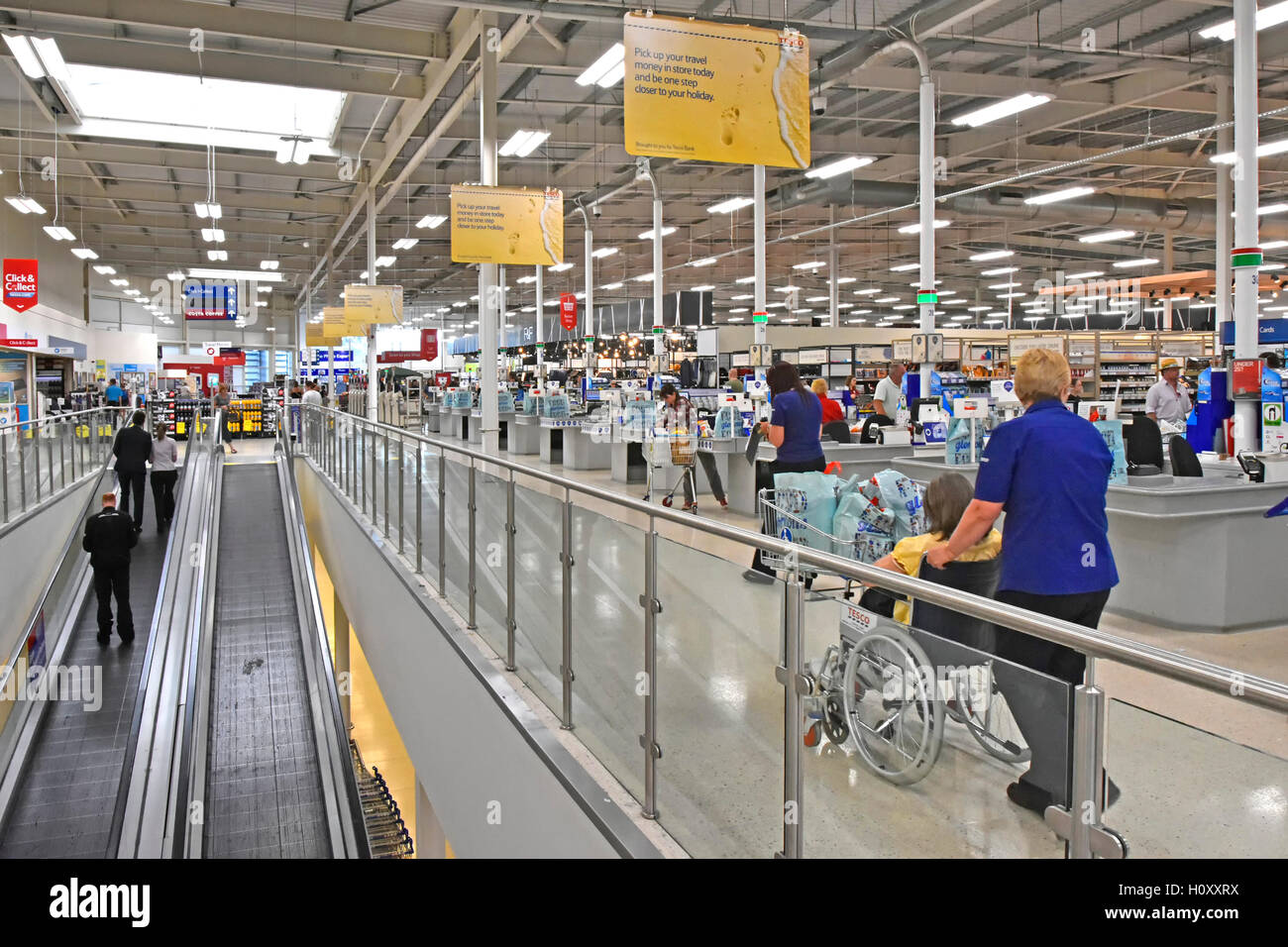 Disability customer service staff & inclined travellators in Tesco supermarket store to access shopping floor - Stock Image