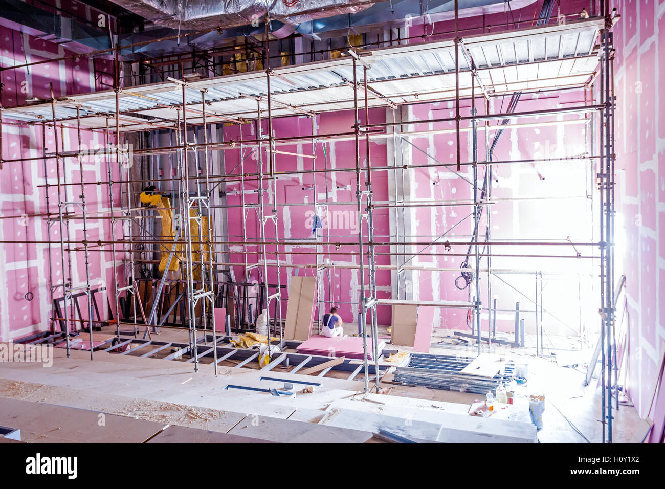 Wonderful Empty Scaffolding Is Placed Against Plasterboard Wall At New Theater With  Back Light From Outside.