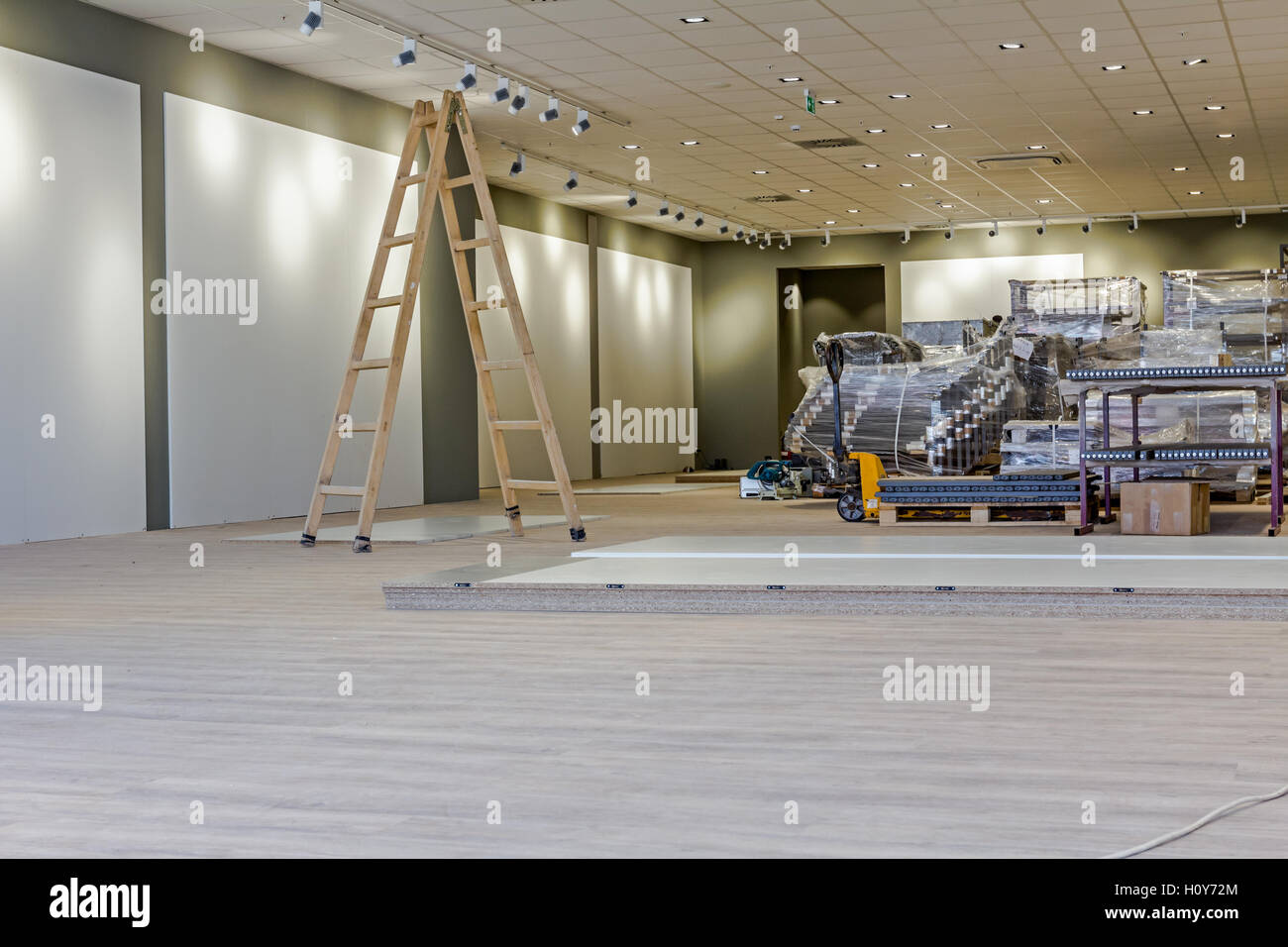 Furnishing equipment is warped in foil for finished modern large showroom with ceiling light. - Stock Image
