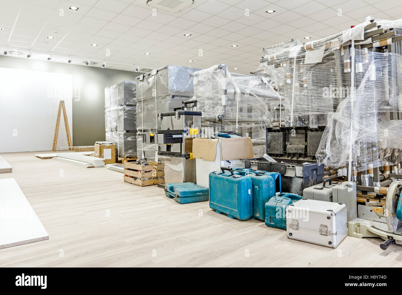 Furnishing equipment is warped in foil for finished modern large showroom with ceiling light, toolkit is on floor. - Stock Image