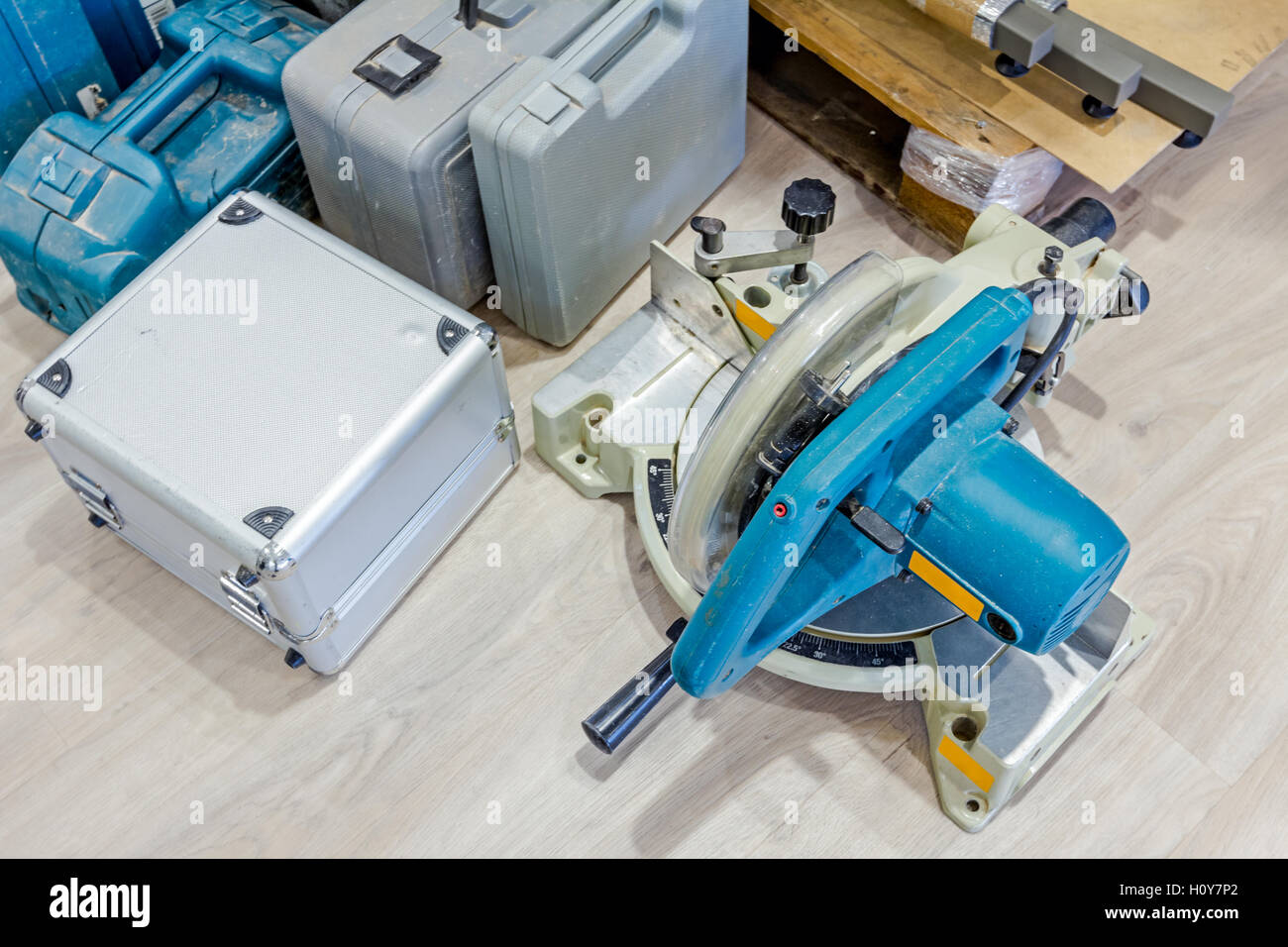 Various plastic tool boxes are on laminate floor with a lot of equipment for furnishing in workshop. - Stock Image