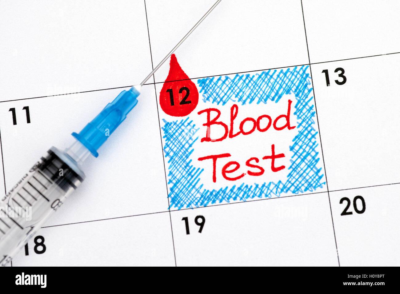 Reminder Blood Test in calendar with syringe. Close up. - Stock Image