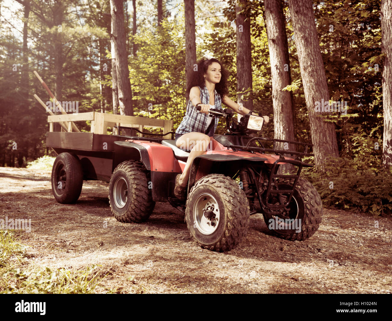 Young farm woman gardener riding an ATV with a trailer along tree lined country road. Muskoka, Ontario, Canada. - Stock Image