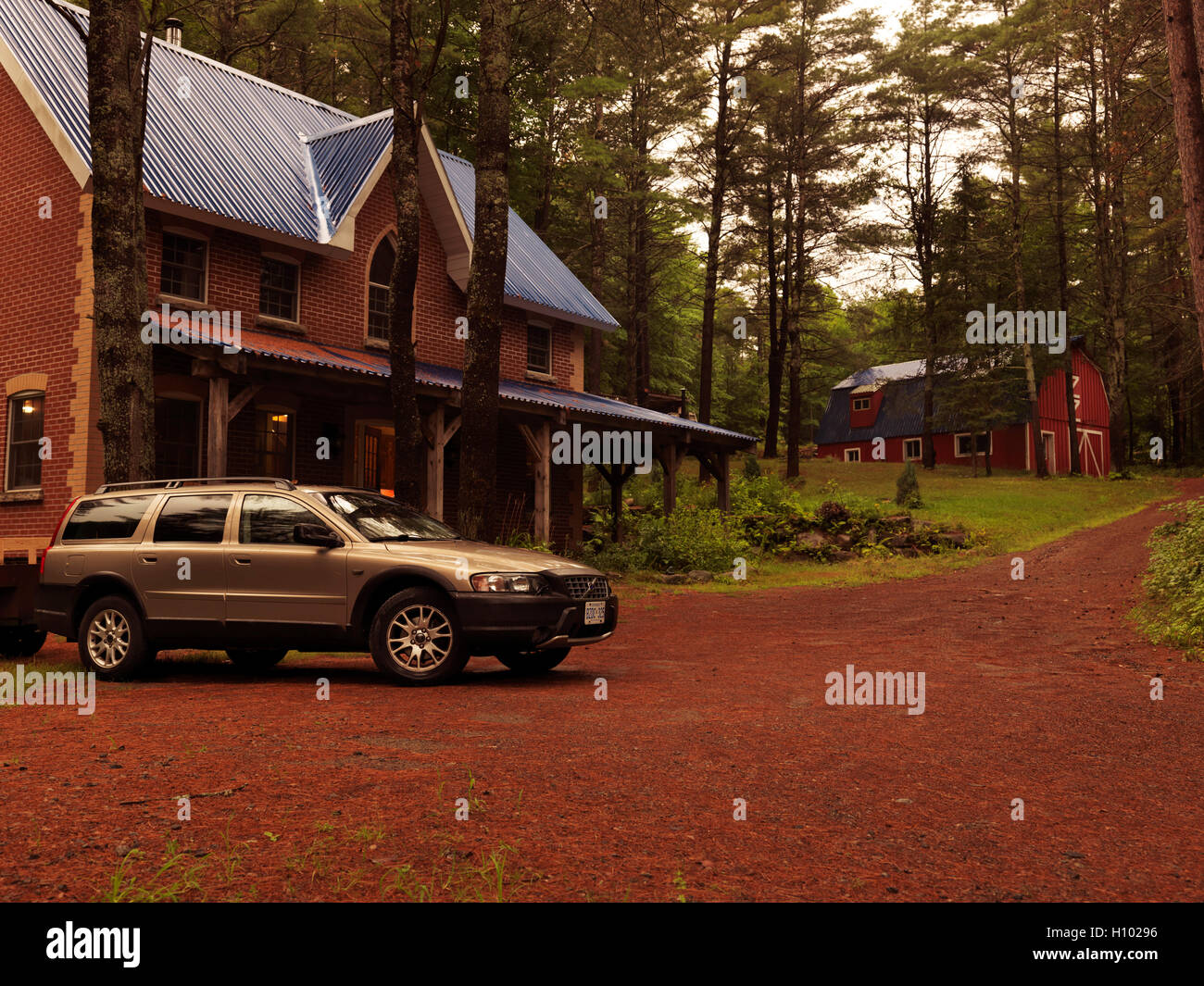Brick country house or cottage and Volvo XC70 station wagon car in Muskoka, Ontario, Canada countryside scenery. - Stock Image