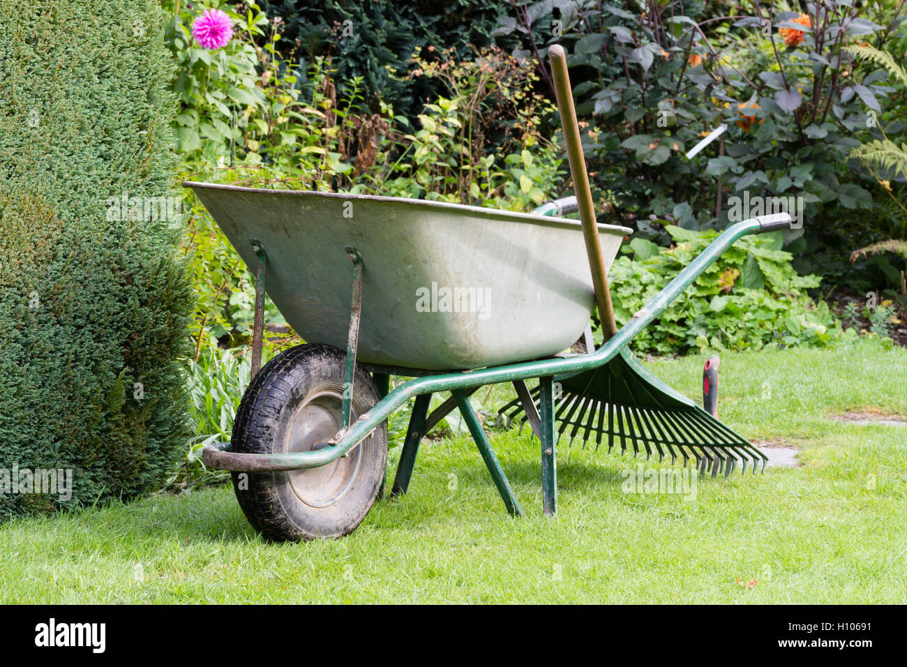 Wheelbarrow, lawn rake and trowel ready for work in a large garden - Stock Image