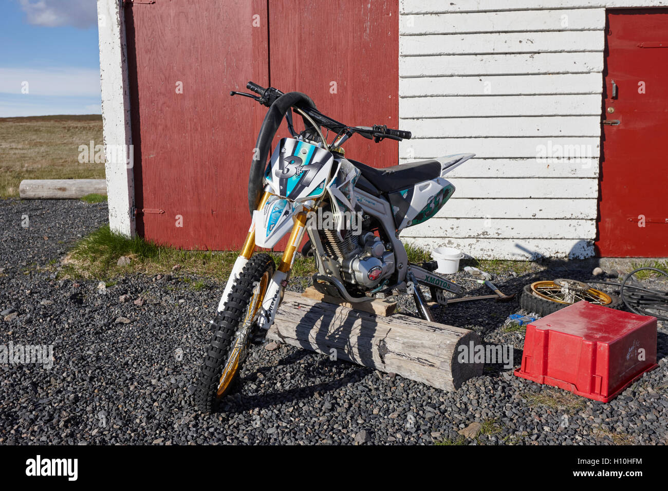 repairing a puncture on a chinese dirt trail bike used by a farmer to herd sheep in Iceland - Stock Image