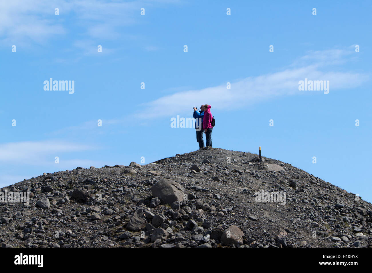 tourists take photos on top of a glacial moraine at jokulsarlon iceland - Stock Image