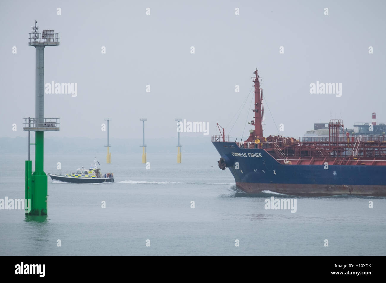 A freight ship, Cumbrian Fisher, sails out of Portsmouth Harbour past the navigation light piles that have been - Stock Image