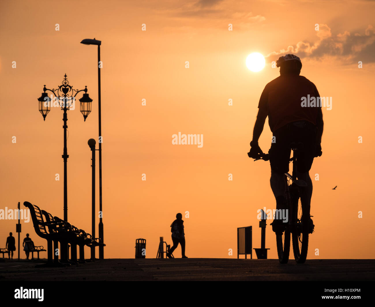 People on Southsea Promenade as the sun rises - Stock Image