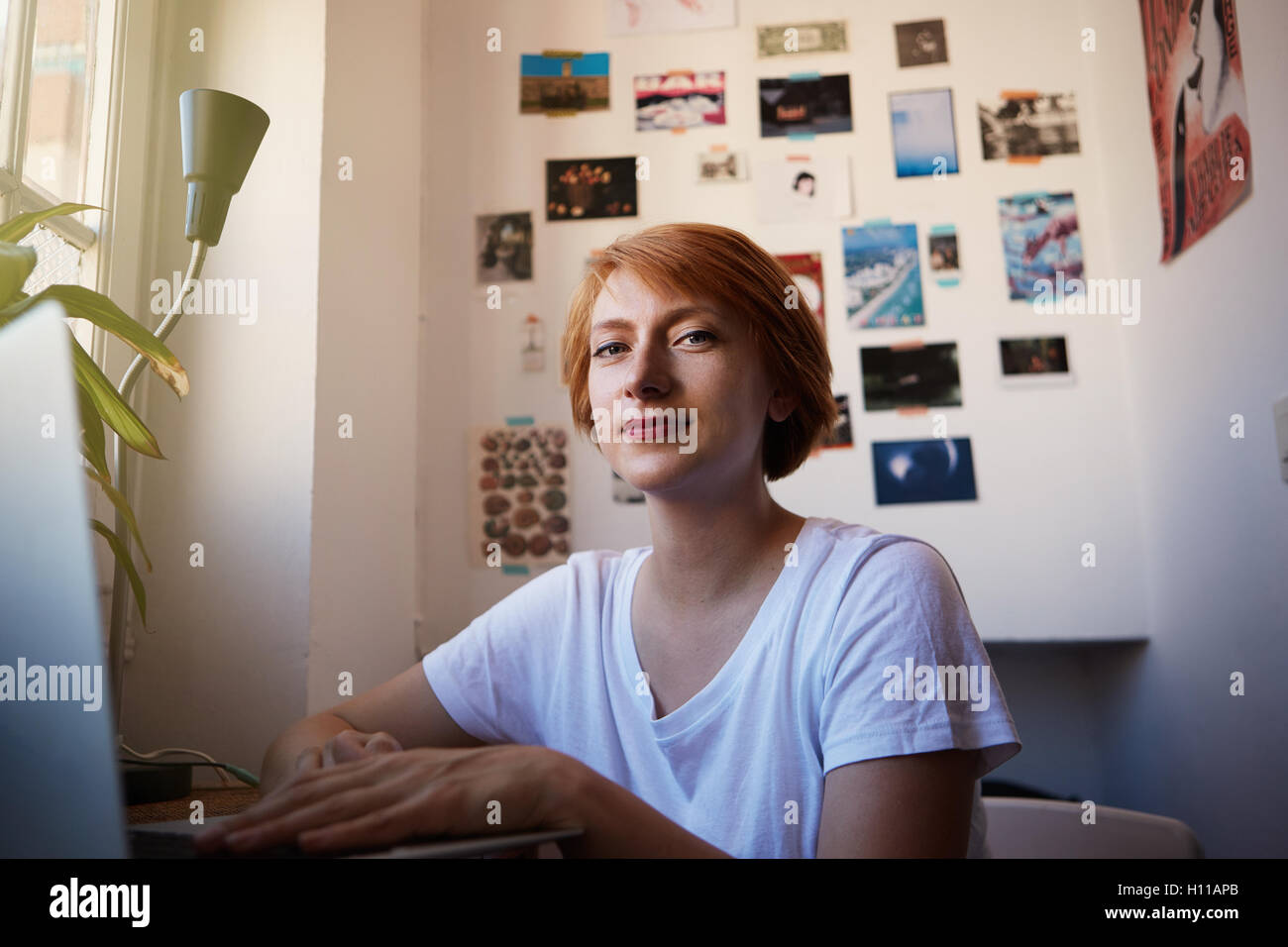One Modern Female Coworker Smiling During Working Process.Young Hipster  Startup Project.Woman short hair and white - Stock Image