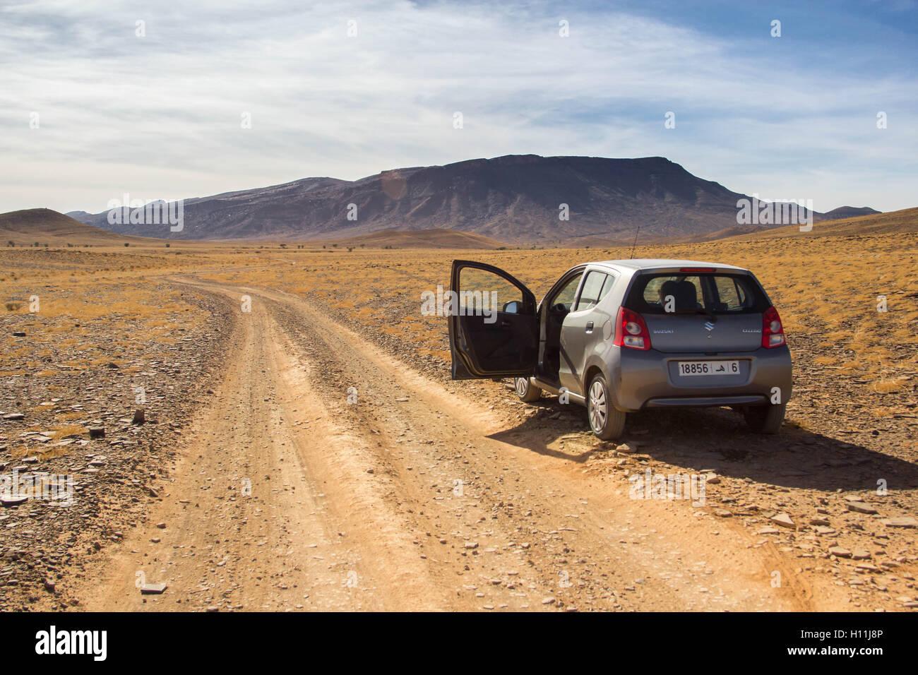 Car in stony desert, Morocco, North Africa - Stock Image