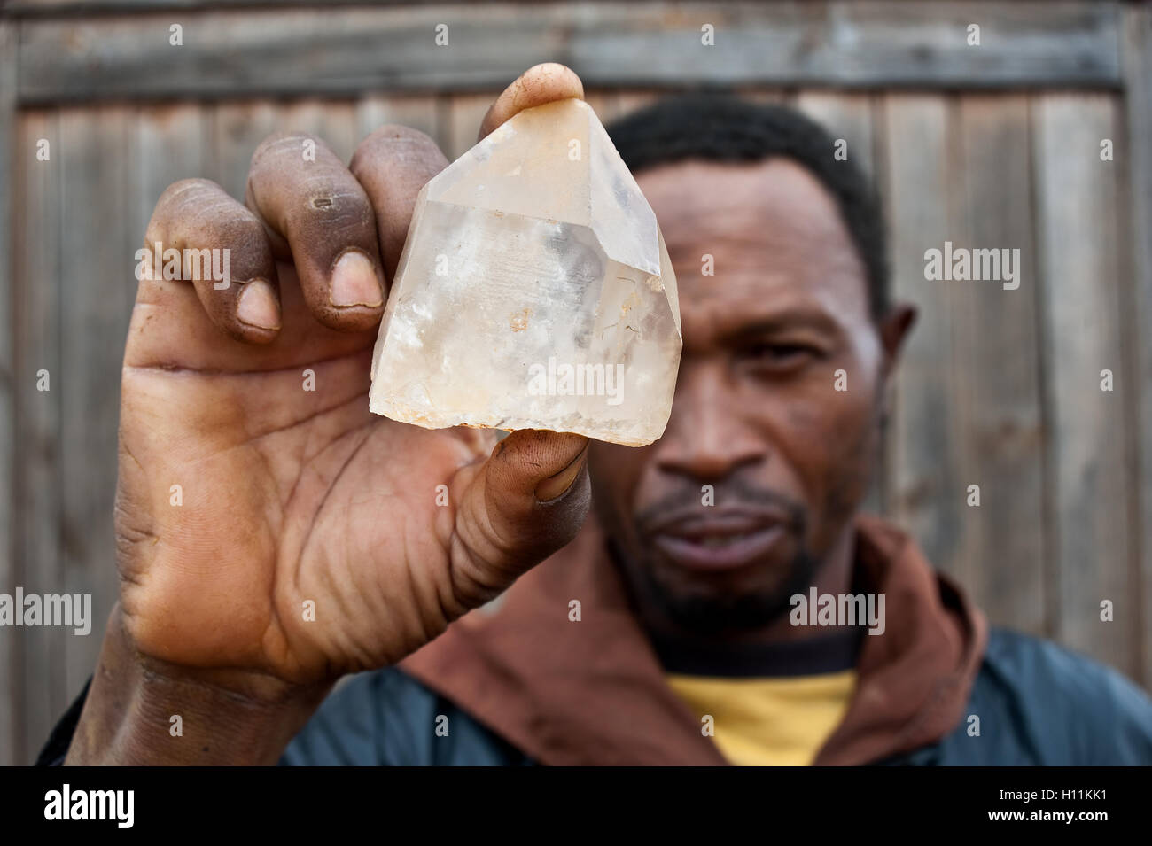 Worker holding rock crystal ( i.e. hyaline quartz) found in a nearby quarry ( Madagascar) - Stock Image