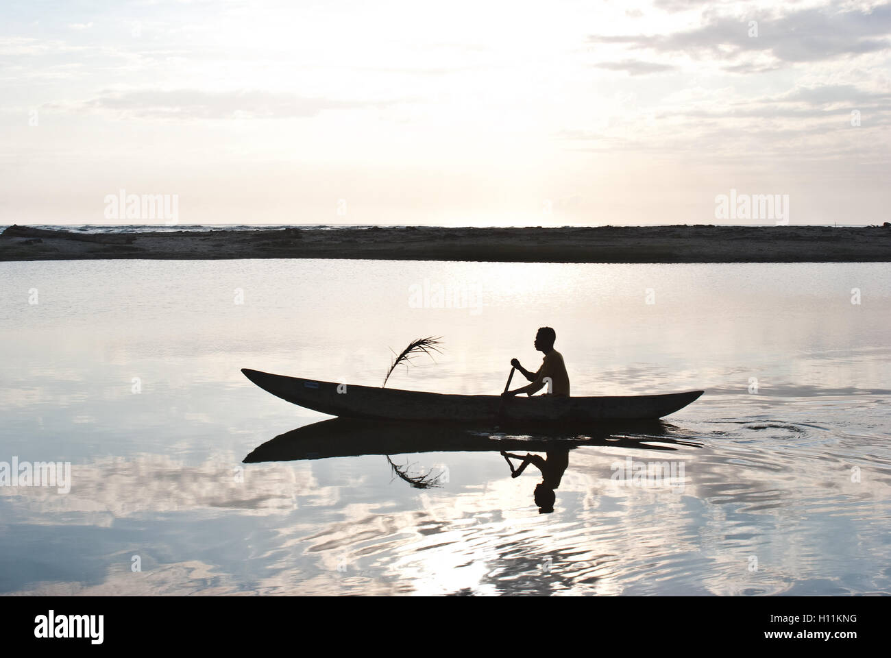 Man boating in the Pangalanes canal. In the background, the Indian ocean is visible ( Madagascar). - Stock Image