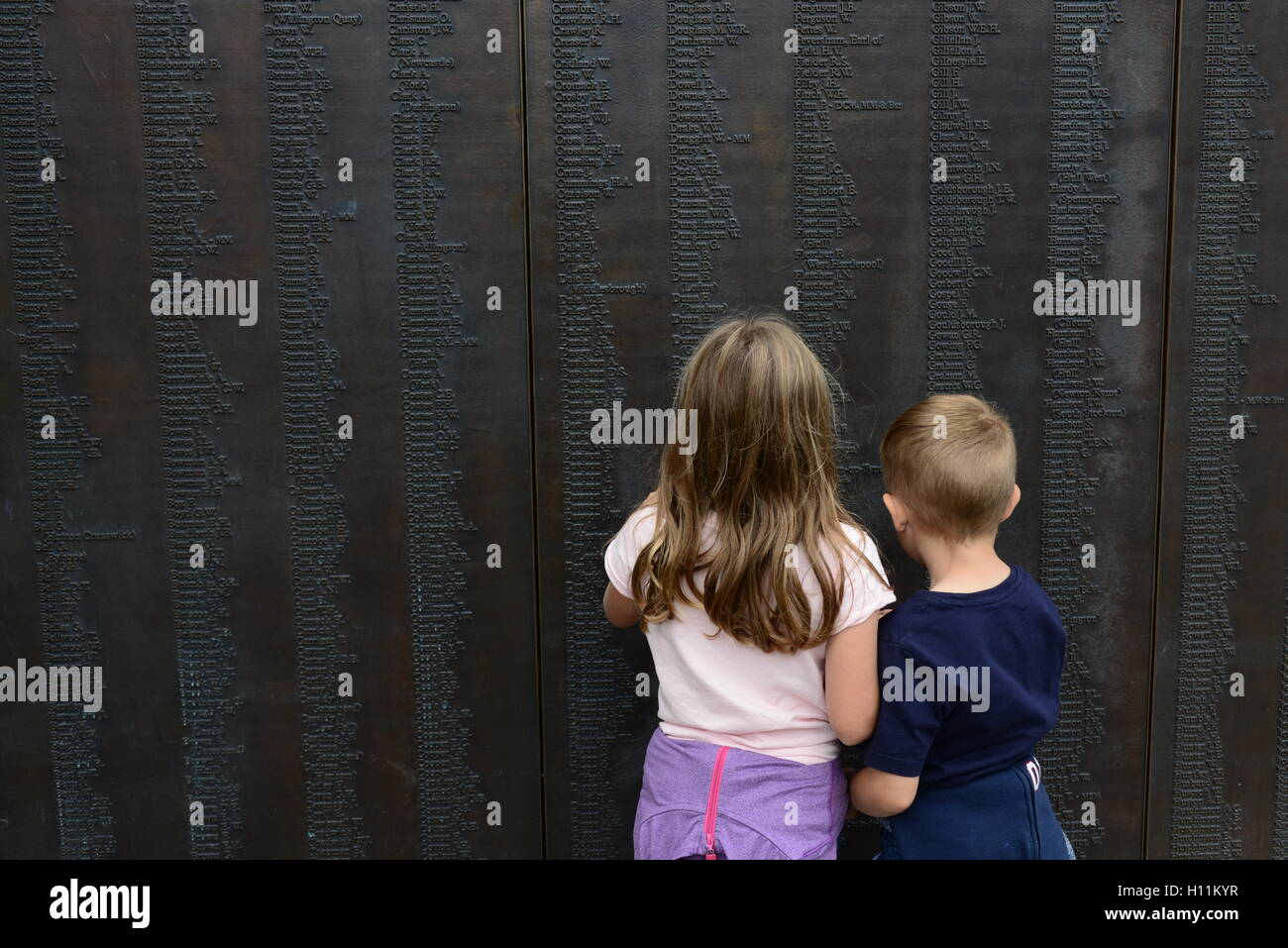 Two children looking at memorial to the North Eastern Railway men who died in World War One, York City Centre, North - Stock Image