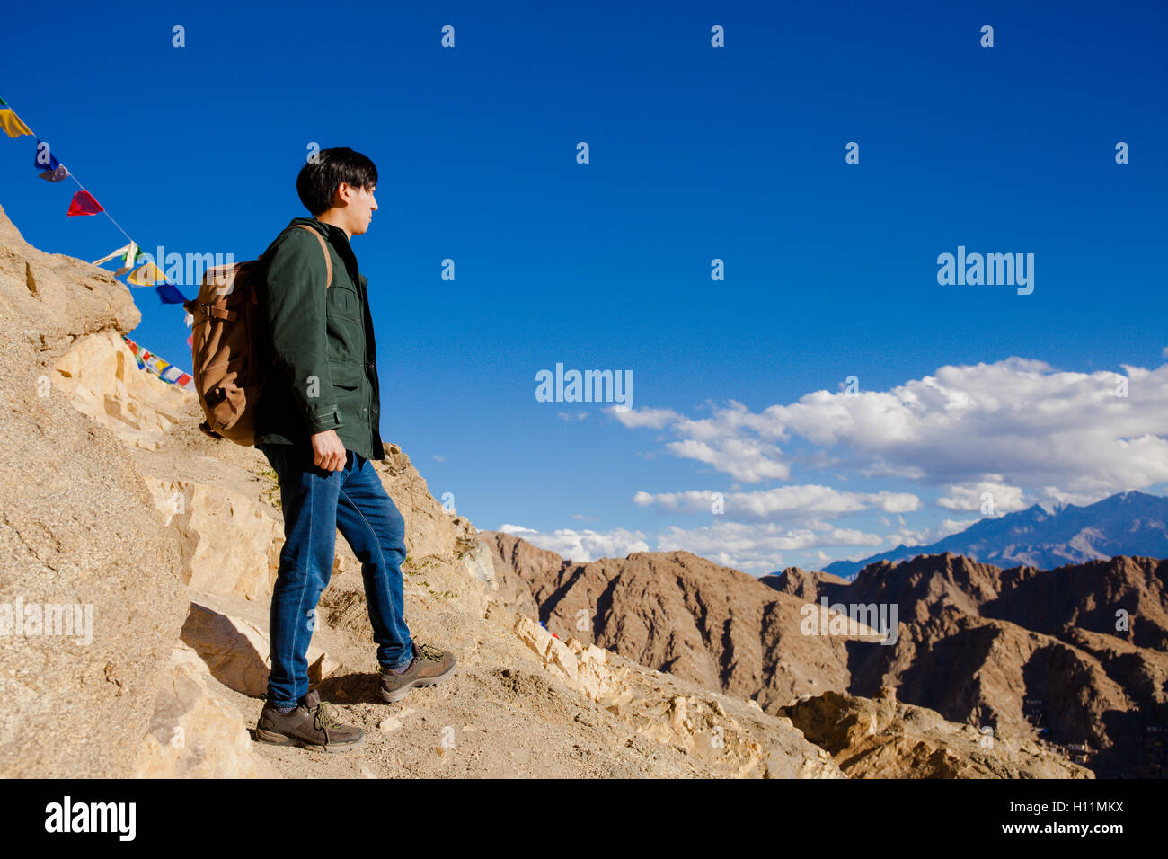 Young Asian traveler standing on high hills and looking away at the village over blue sky background in Leh, Ladakh, Stock Photo