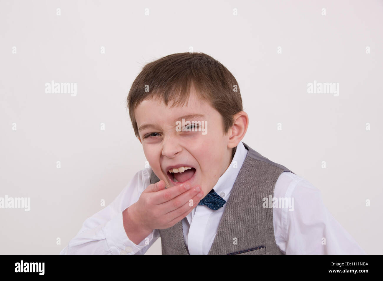 Portrait of a laughing young man : 8 year old boy wearing formal bow tie and waistcoat - Stock Image