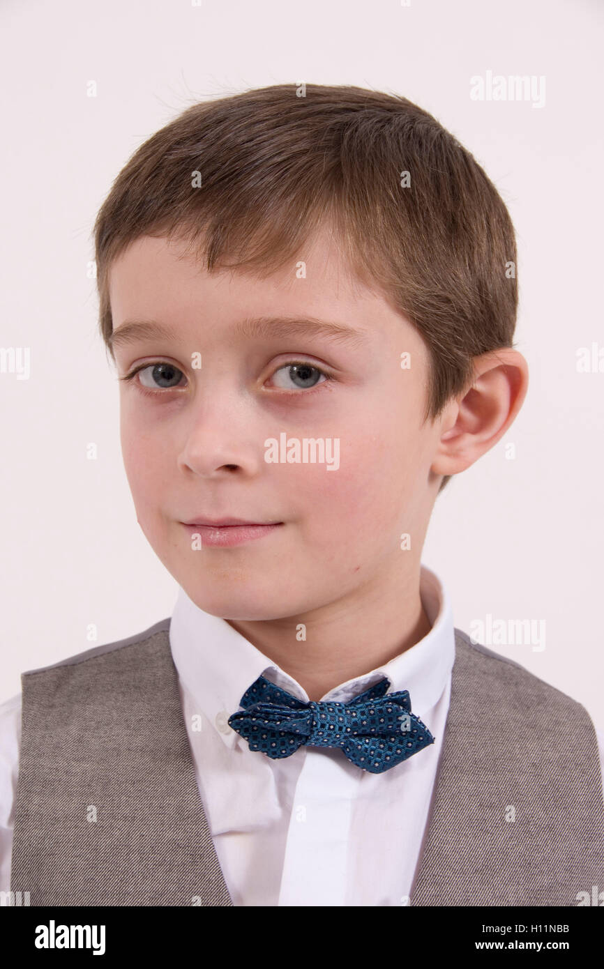 Portrait of an inscrutable young man : 8 year old boy wearing formal bow tie and waistcoat - Stock Image
