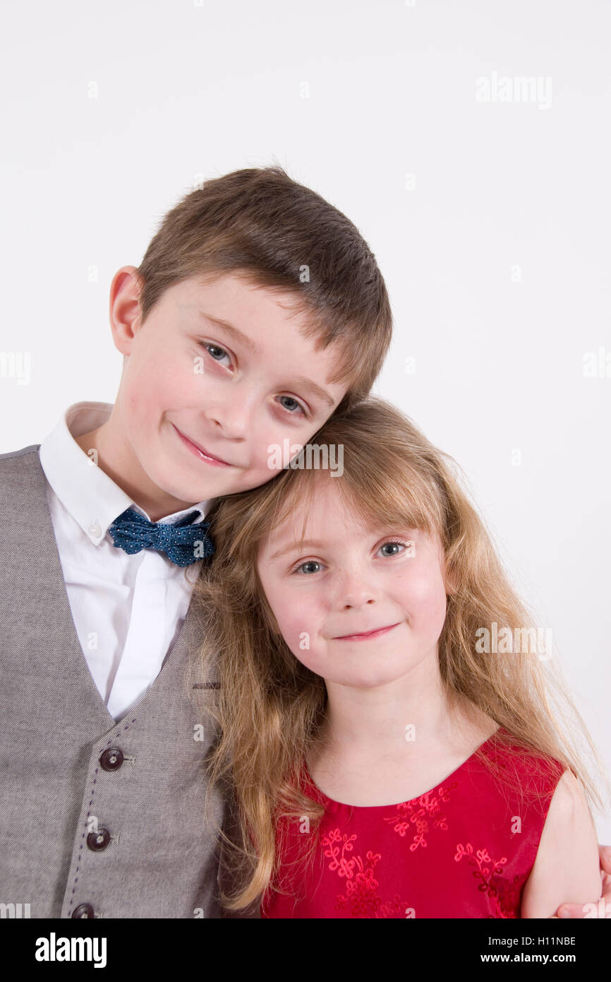 Siblings : 7 year old boy & younger sister aged 6 wearing formal evening dress, studio portrait isolated on - Stock Image