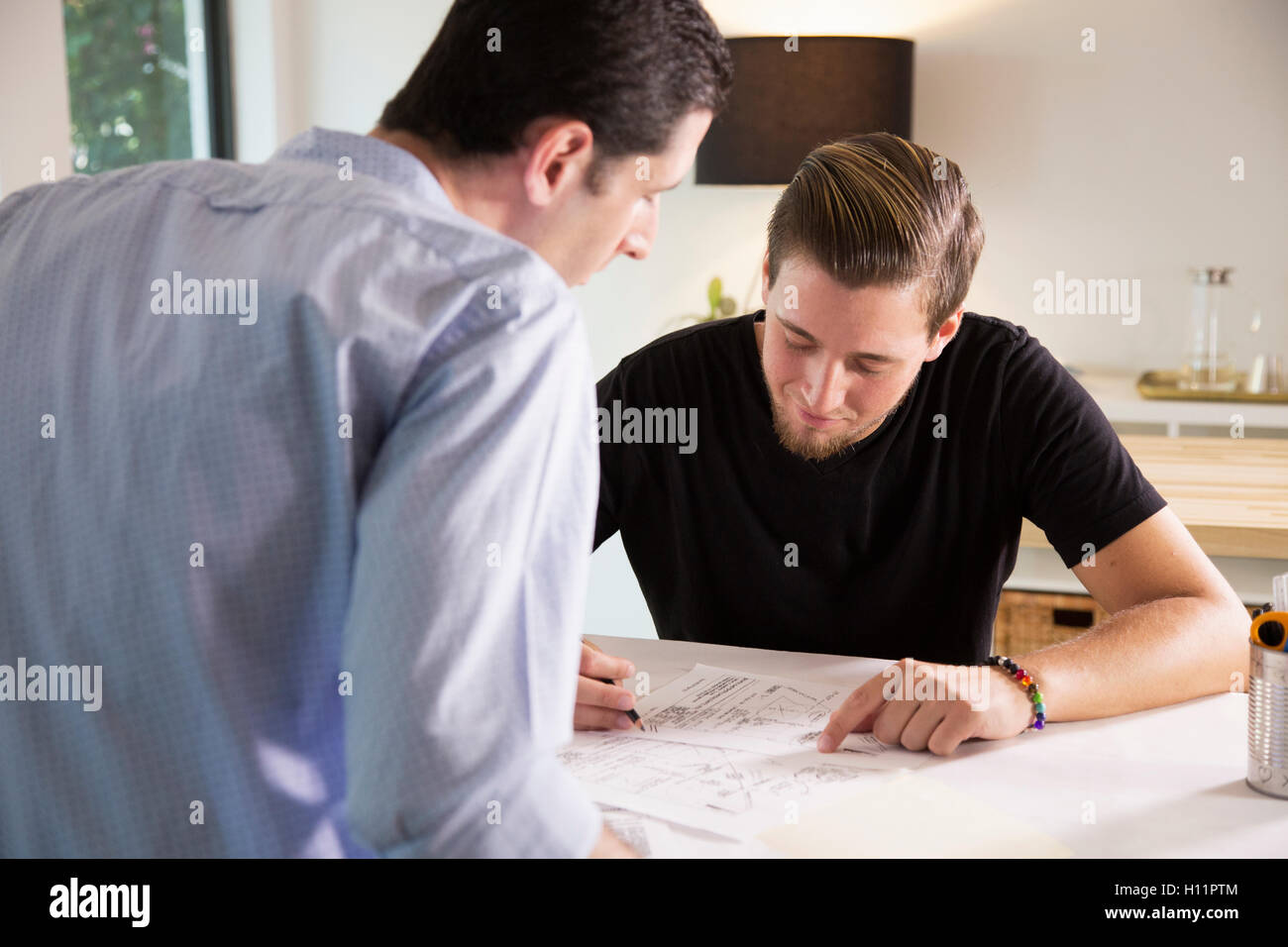 Two male office workers sharing ideas in a modern office Stock Photo