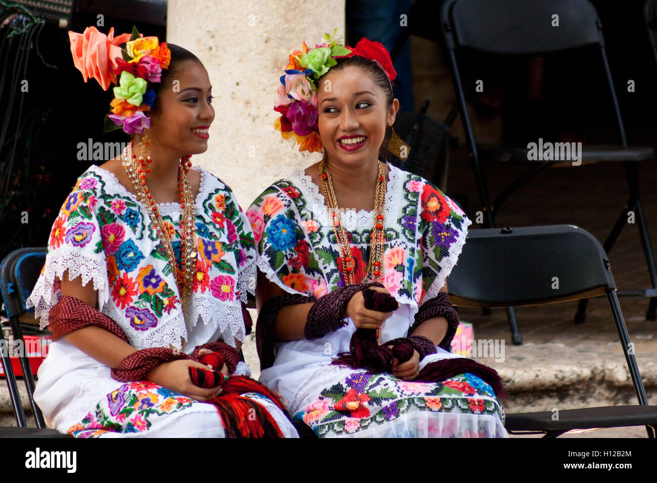 Two yucatecan girls talking to each other waiting for his turn to dance in the city festival 'La vaqueria' - Stock Image