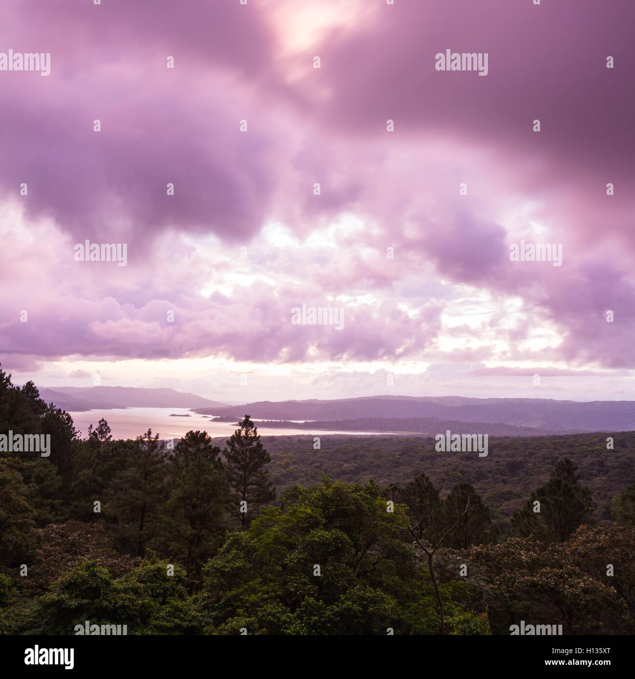 sunsetting behind Lake Arenal viewed from an elevated viewpoint above the tree tops - Stock Image