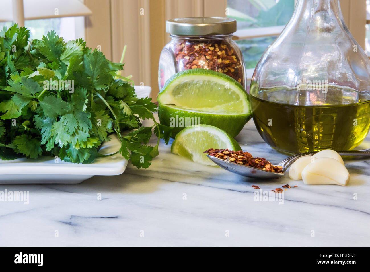 Mexican food ingredients in a kitchen on a marble top . Cilantro red pepper flakes lime garlic olive oil - Stock Image