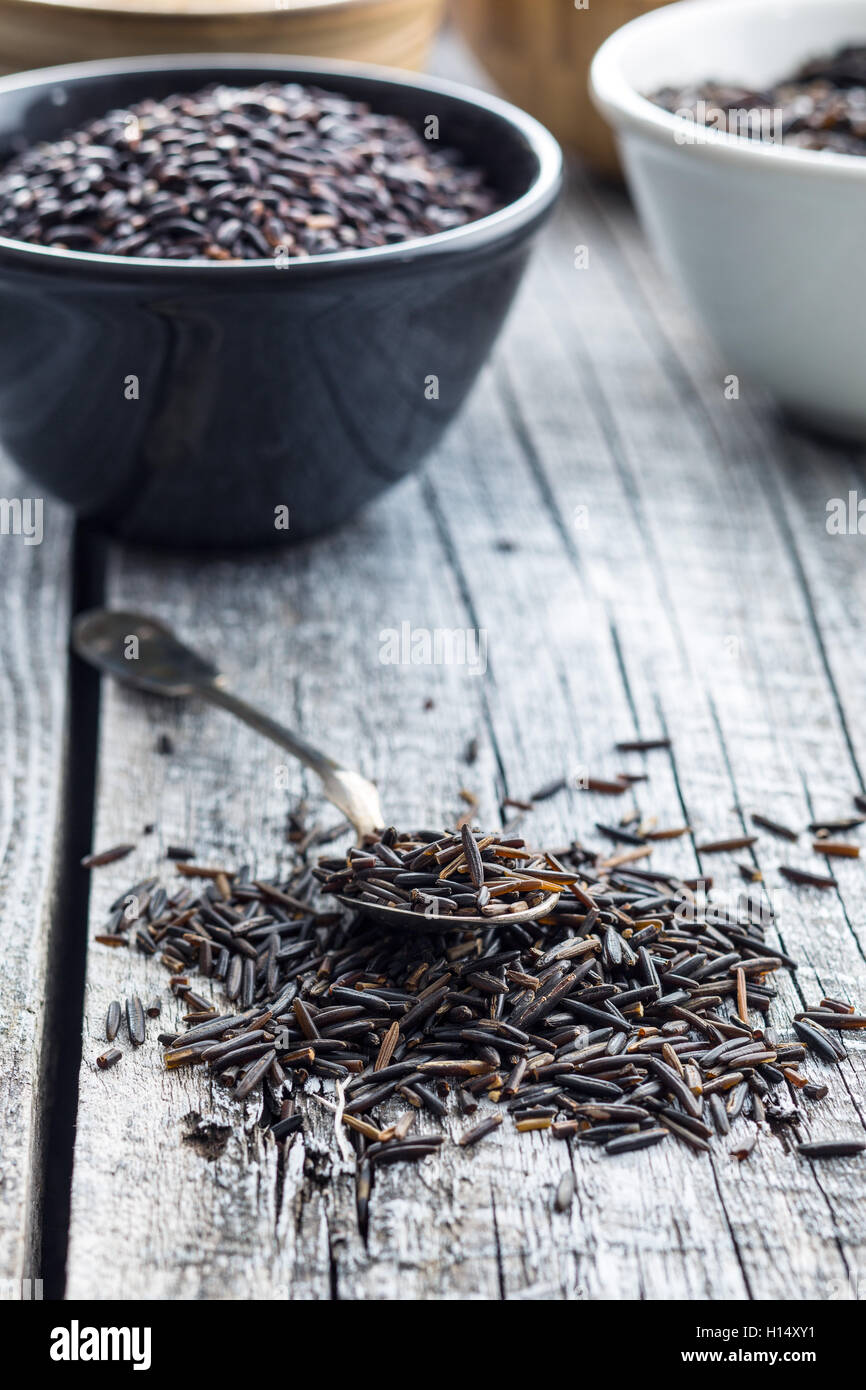 The wild rice in spoon on old wooden table. - Stock Image