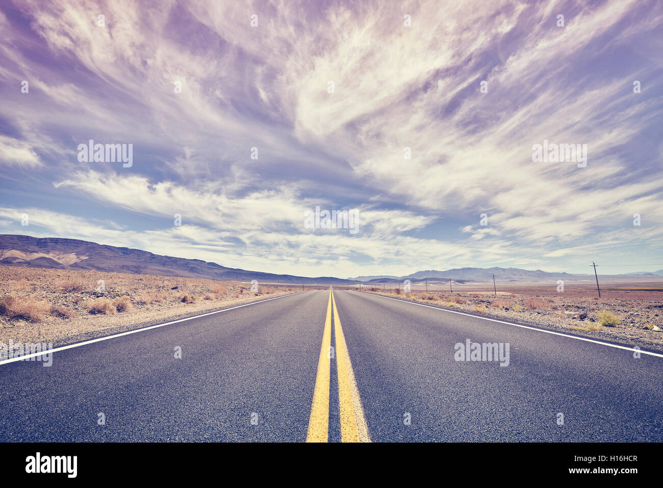 Endless desert road in Death Valley, rose quartz and serenity color toned, travel concept, USA. - Stock Image