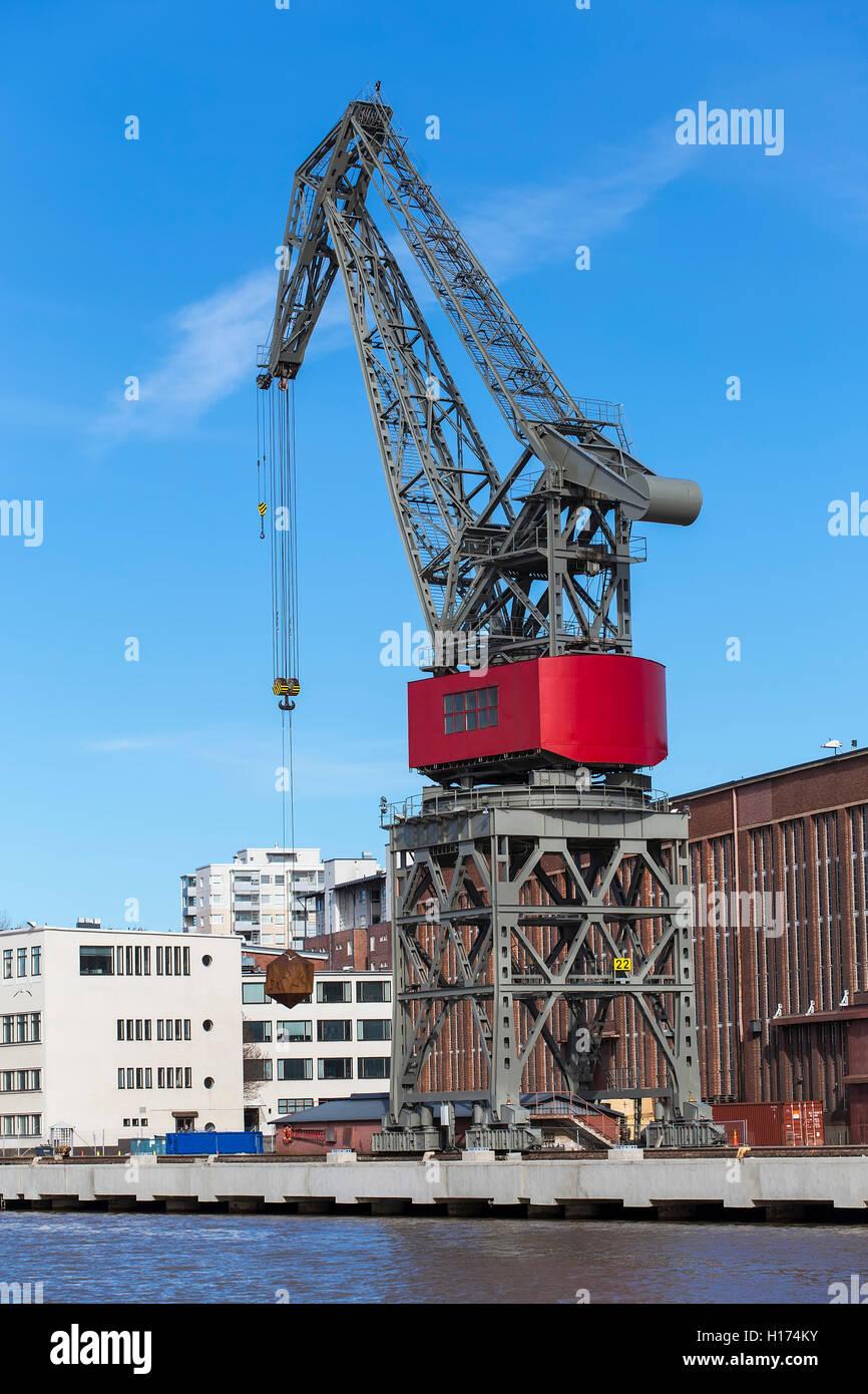 Dockside crane for loading bulk cargo on the quay of the river - Stock Image