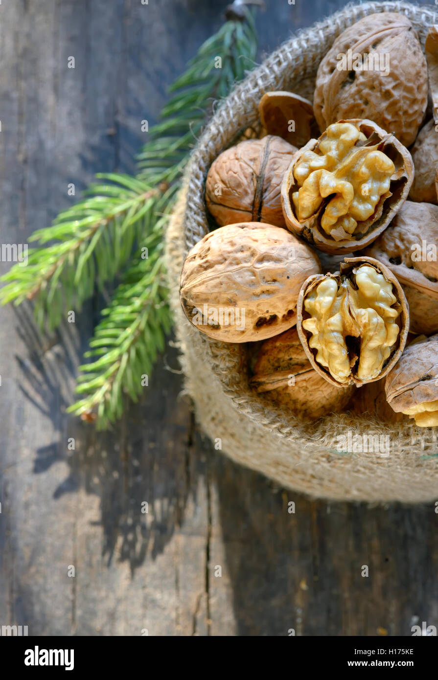 walnuts in a bag on a wooden background - Stock Image