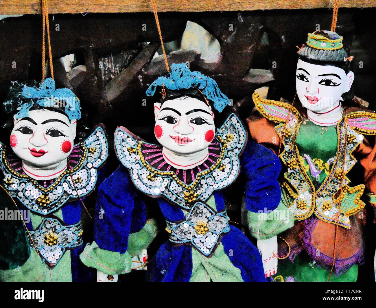 Close up of three brightly coloured hand-made traditional Burmese string puppets - Stock Image