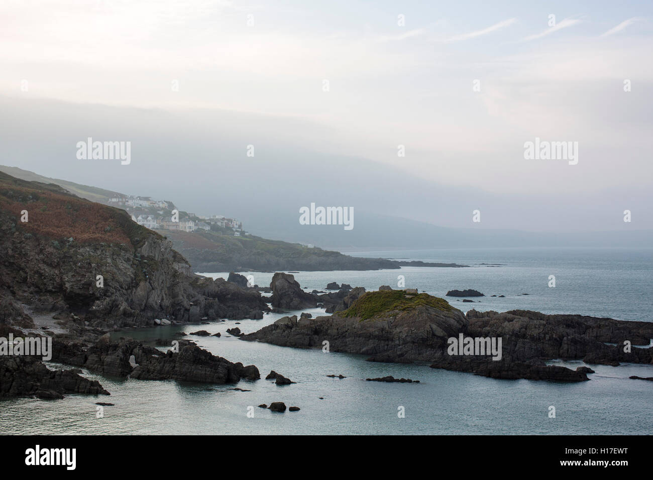 Grey misty coastline with rocks and houses on the south coast of the uk at Woolacombe adn Morthoe. - Stock Image