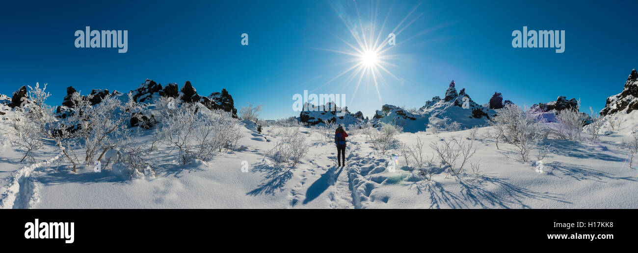 Woman on trail in snowy landscape, sunshine, lava field covered in snow, Krafla volcanic system, Dimmuborgir National - Stock Image