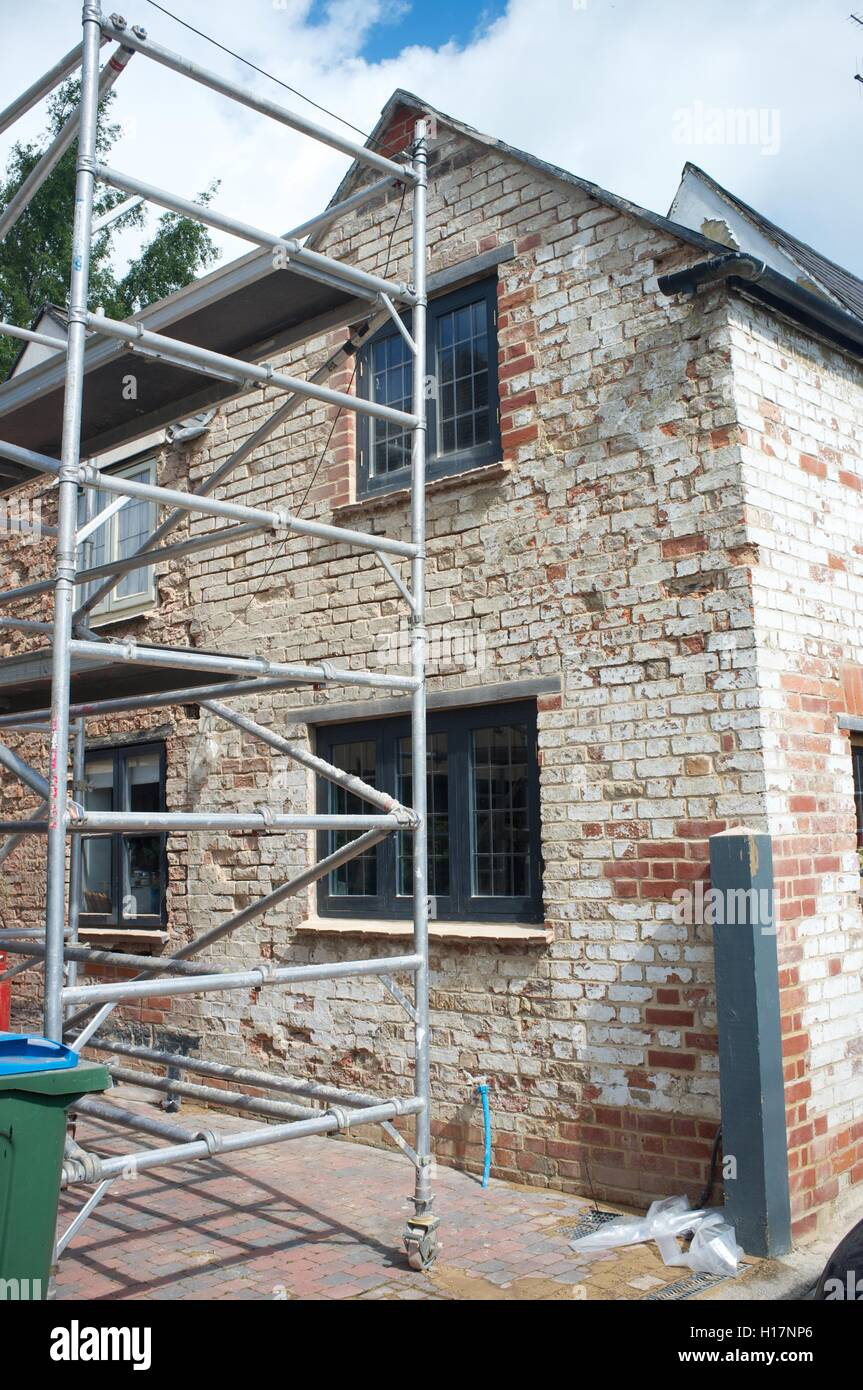 Renovation of exterior of old cottage - Stock Image