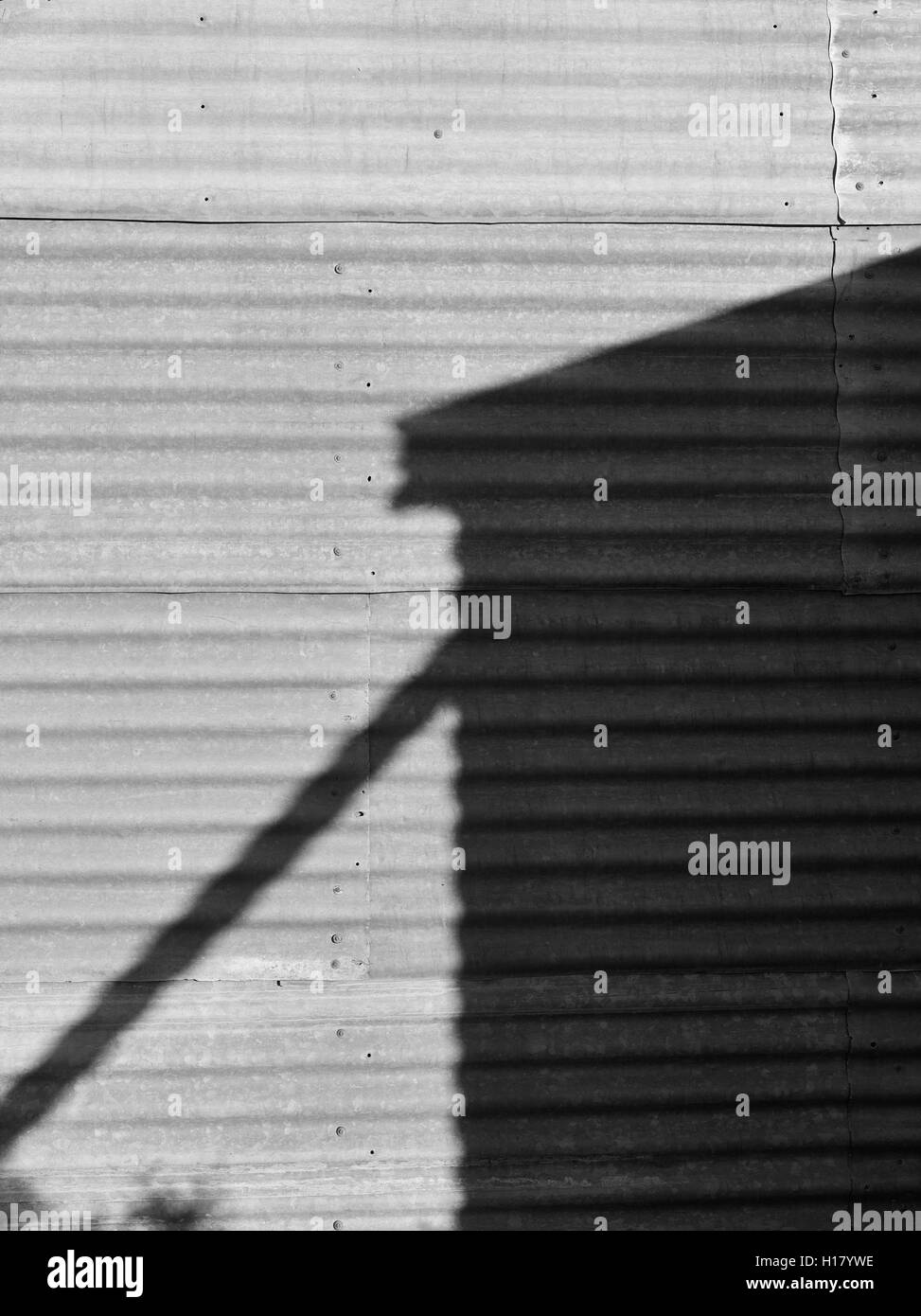 Black and white image outback Australia. Shadow of water tank on corrugated iron wall. - Stock Image