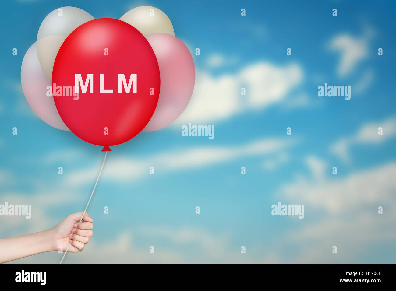 Hand Holding MLM or Multi level marketing Balloon with sky blurred background Stock Photo