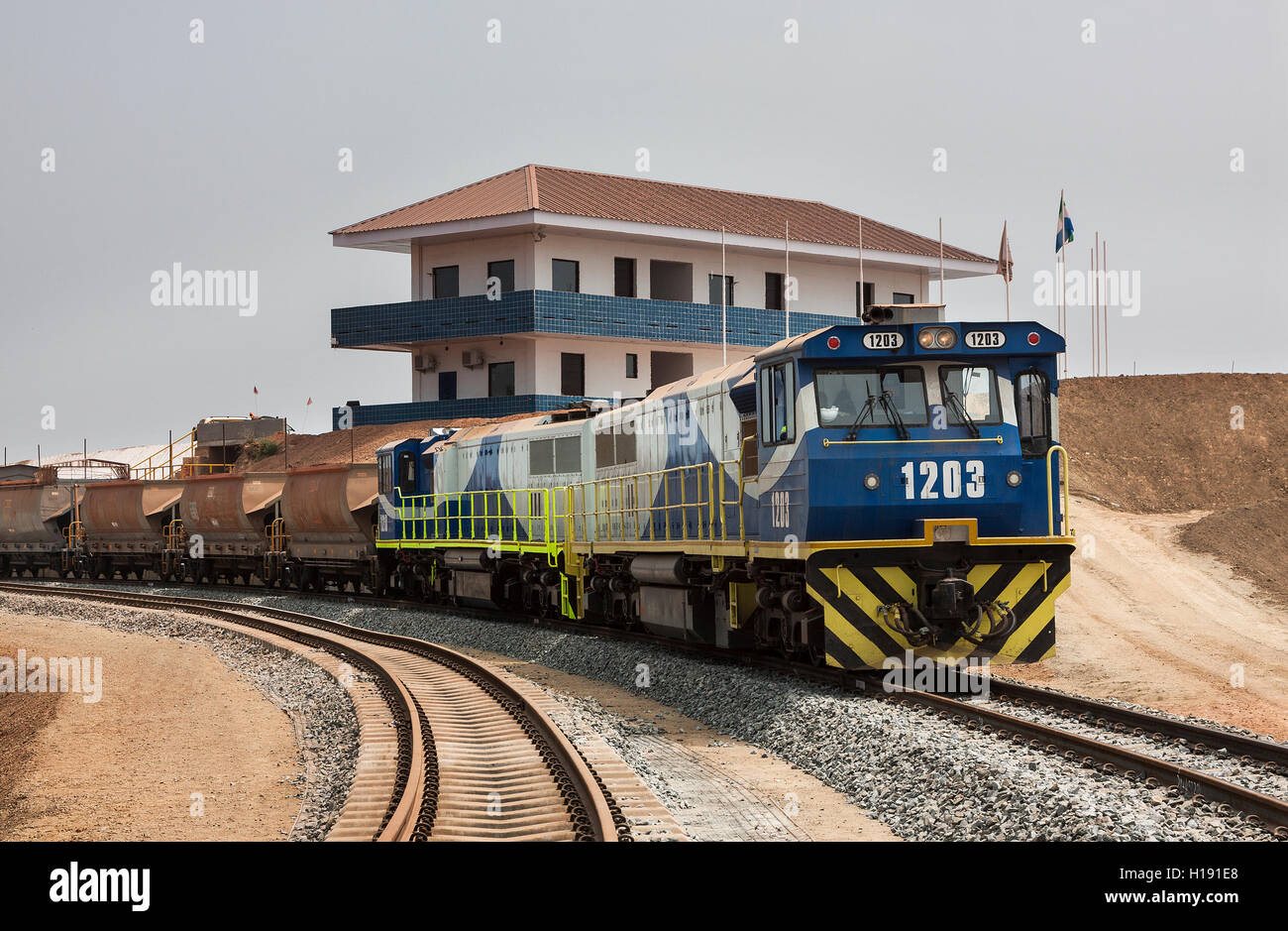 Port operations for managing and transporting iron ore. Grinwell locomotive and ore train on rail train line loop - Stock Image