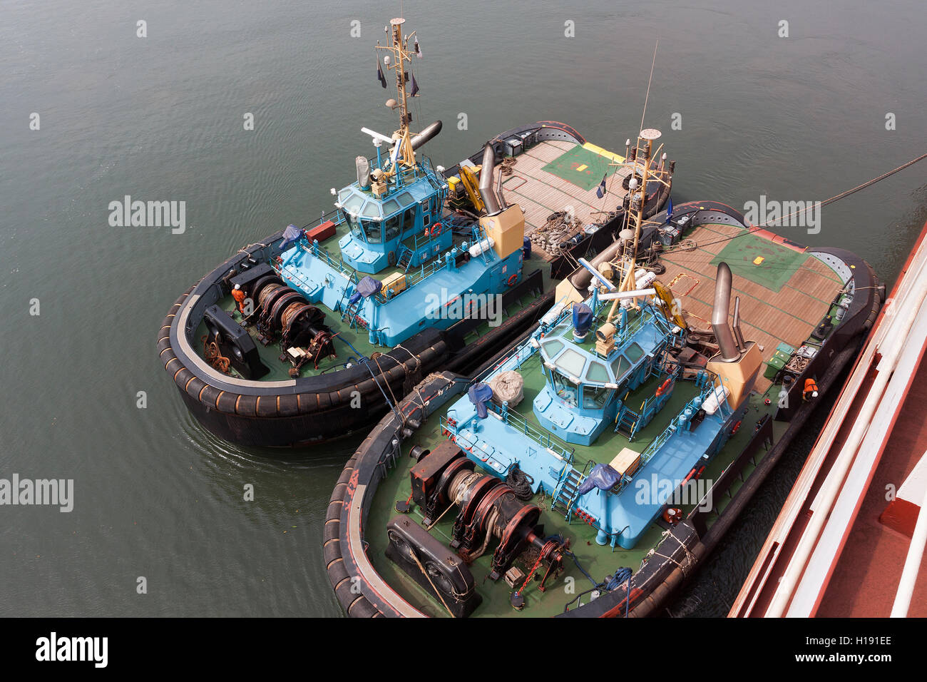 Marine and port operations from jetty.Two tugs tied up and waiting for cargo boat to sail so they can move and guide - Stock Image