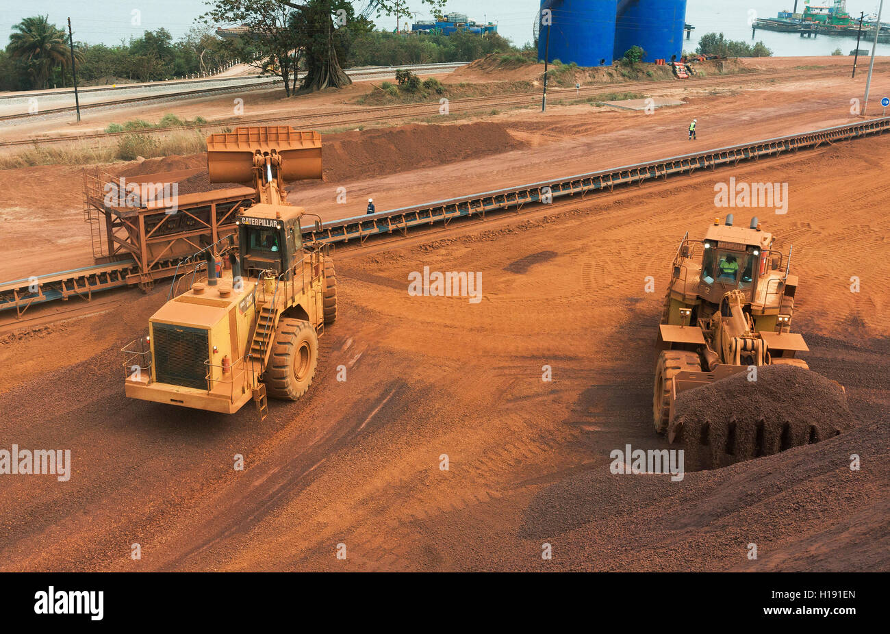 2 Front end loaders loading hopper with lump iron ore from reclaimed stack behind. Ore then passes onto conveyor Stock Photo