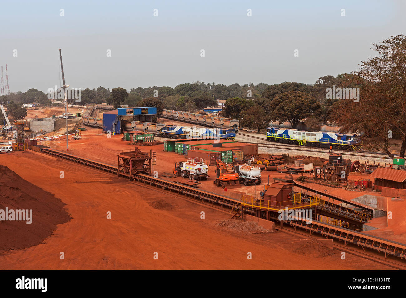 Port operations for managing and transporting iron ore. Marshalling yard and train unloading in dumping area. Conveyor - Stock Image